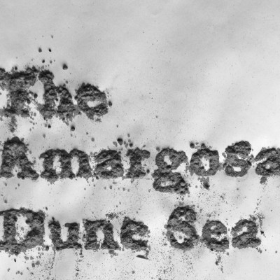 "Title (""The Amargosa Dune Sea"") written into sand"