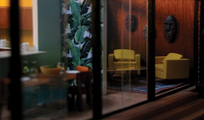 Photo of the interior of a built miniature house, peering into a glass-walled room with leafy wallpaper, two yellow chairs, and masks on the walls.