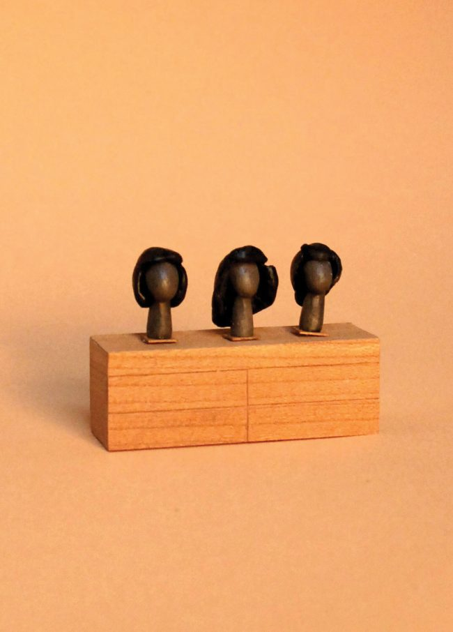 Photo of a built miniature dresser where wigs sit on mannequin heads.