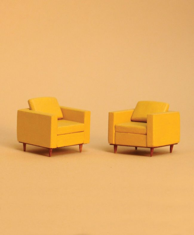 Photo of two built miniature yellow armchairs.