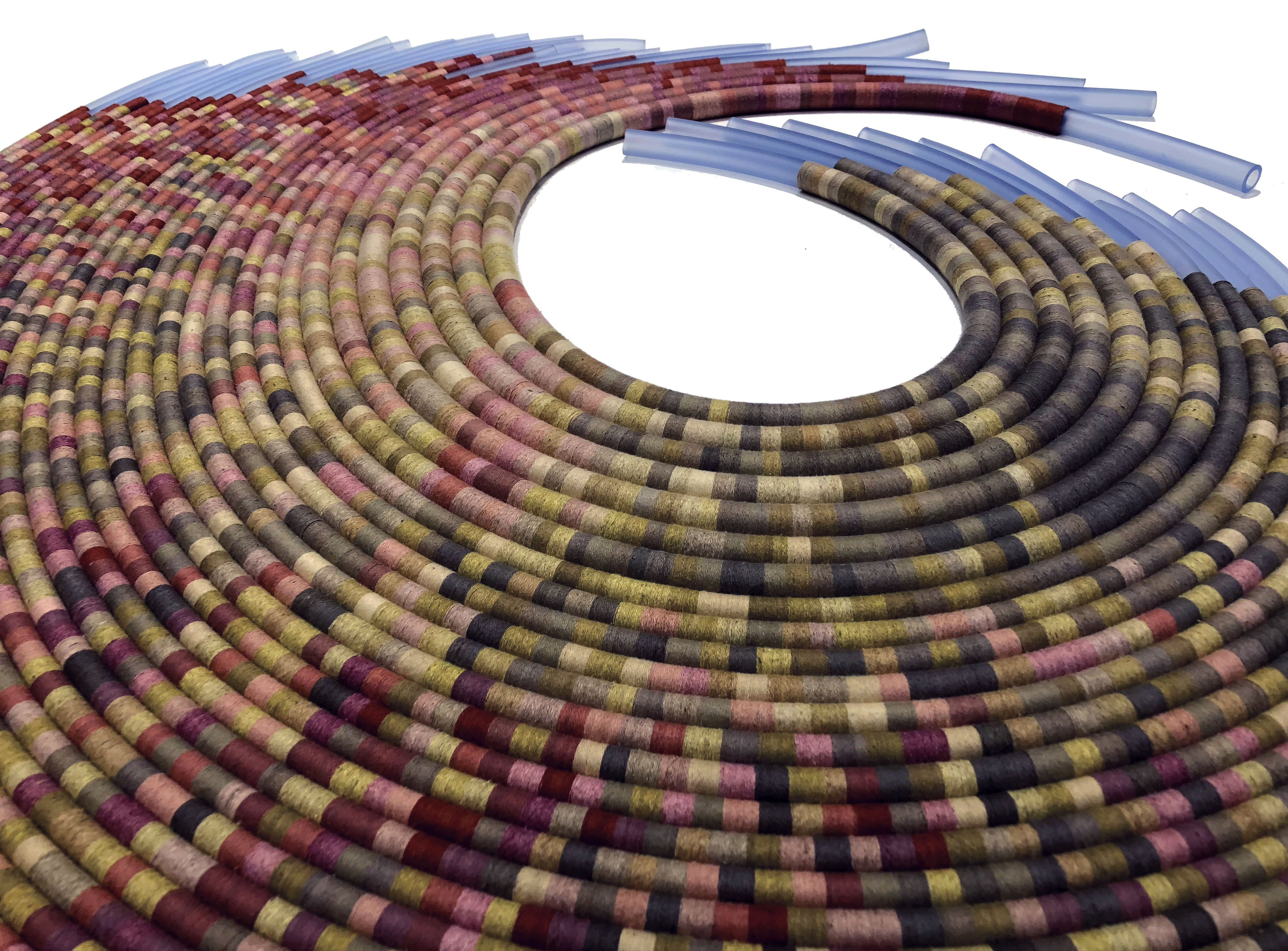Photo of varying lengths of medical tubing lying on a surface, each one wrapped in colored thread and nested to create a circular swoop.