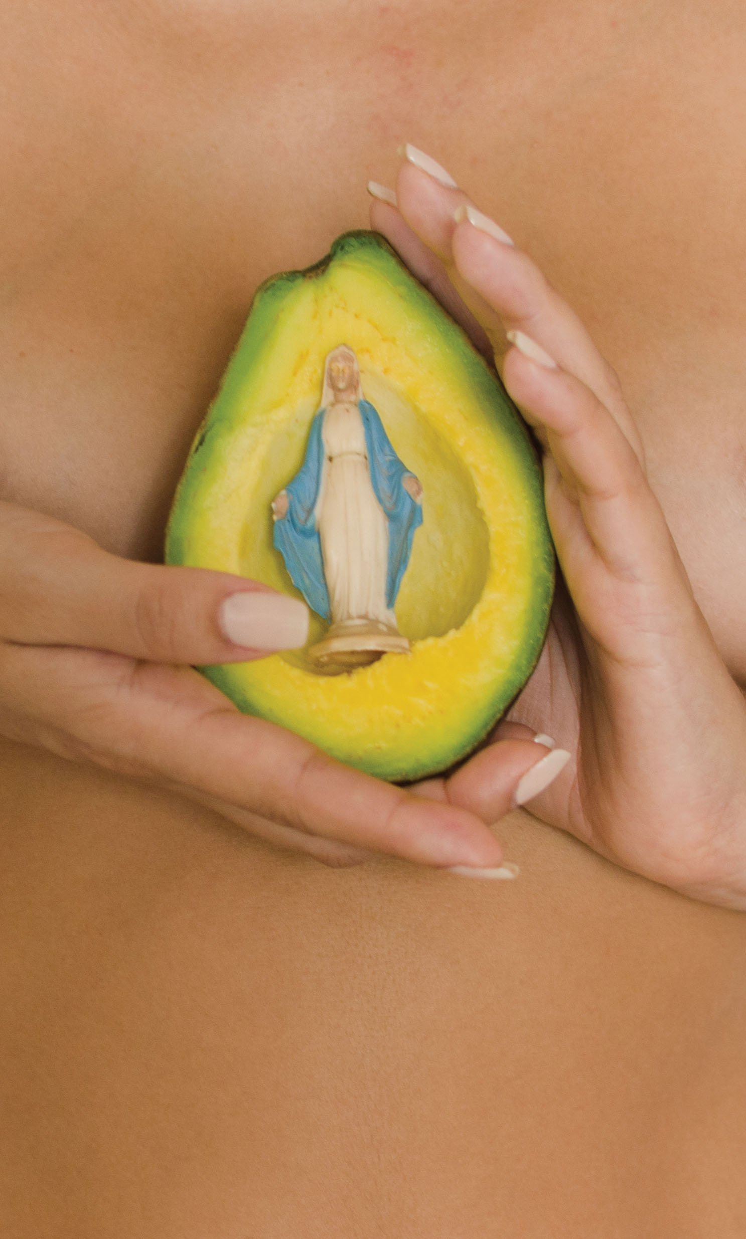 Closeup image of a woman's hands holding, between her breasts, a scooped-out avocado with a Virgin Mary figurine inside.