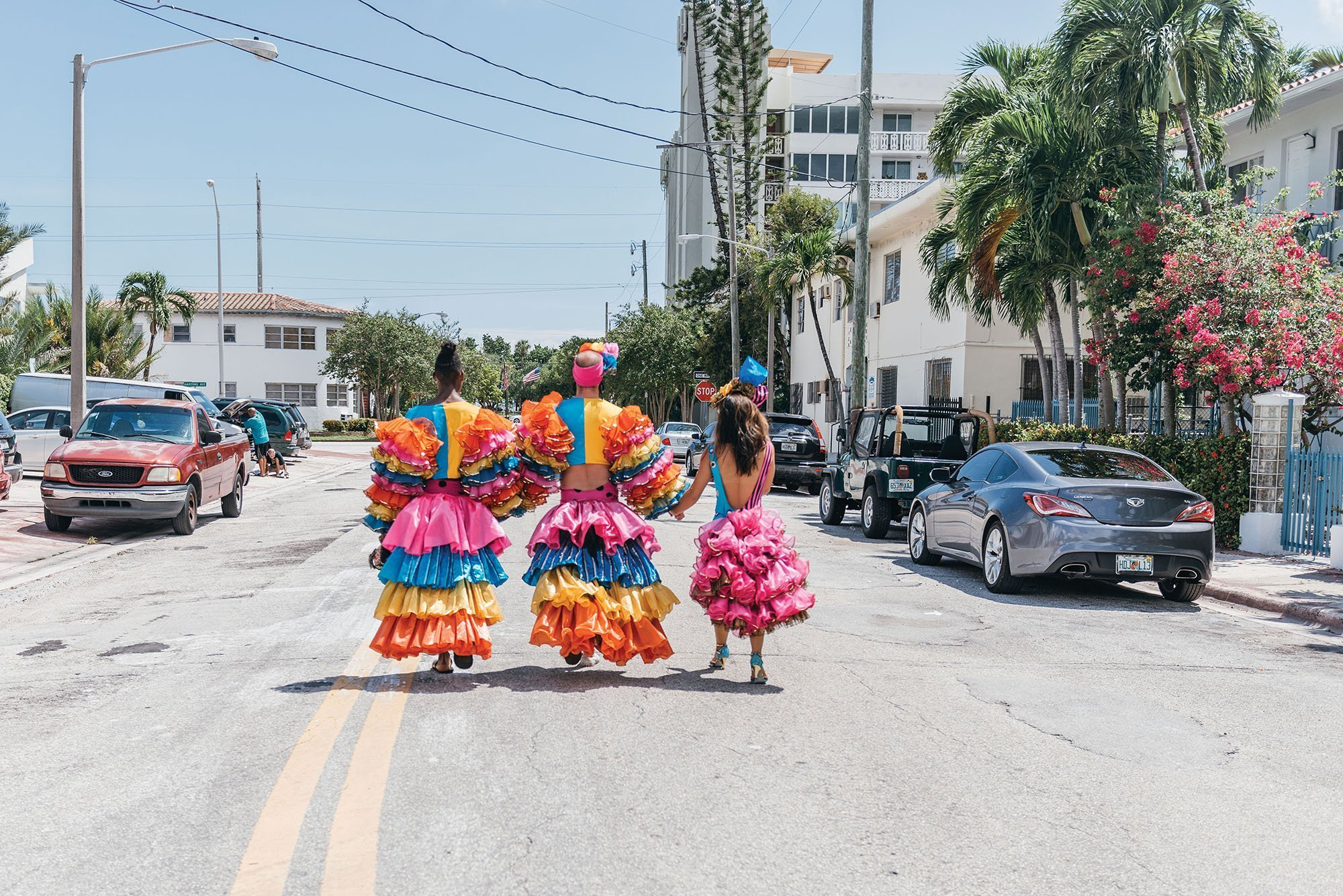Photo of three dancers wearing colorful and ruffly flamenco costumes, walking away from the camera down a Miami street