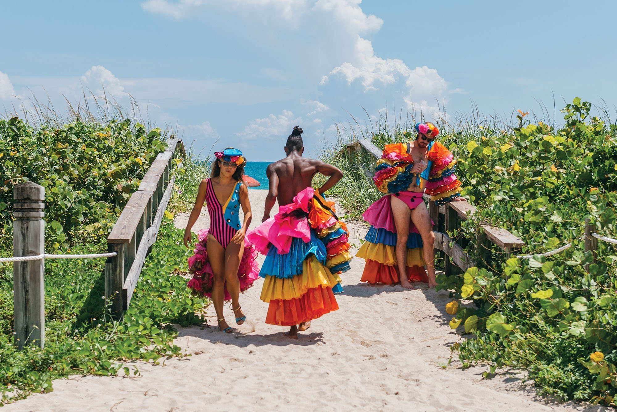 Photo of three dancers in ruffly flamenco costumes (orange, yellow, and blue) walking in the sand on a path to the beach