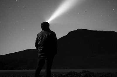 Image of a man standing with his back facing the camera, shining a headlamp into the night sky