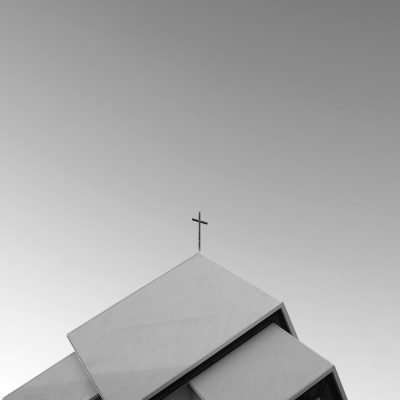 A black-and-white image of the roof of a church, with a cross reaching into a wide sky.