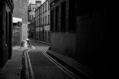 A dark alleyway between brick buildings