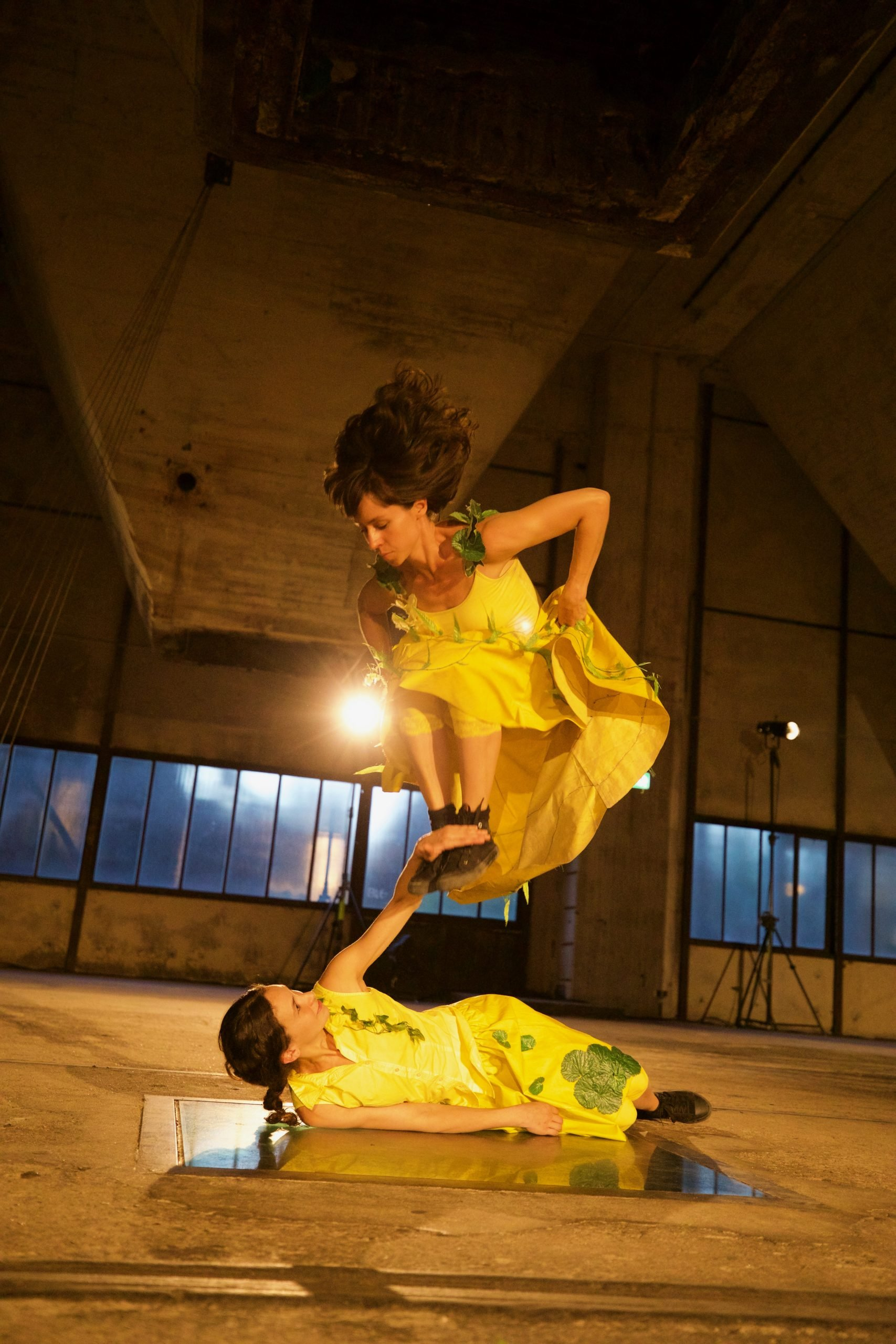 Two dancers in yellow appear in a warehouse at night. One jumps, lifting her feet, over the other, who is lying down.