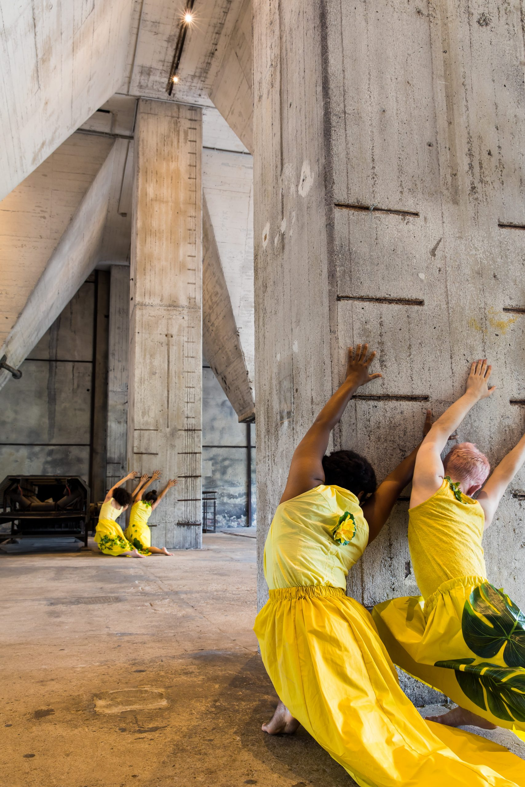 Dancers in yellow lean against pillars in a large concrete space, hands up and facing away from the camera, arching their bodies to the left.