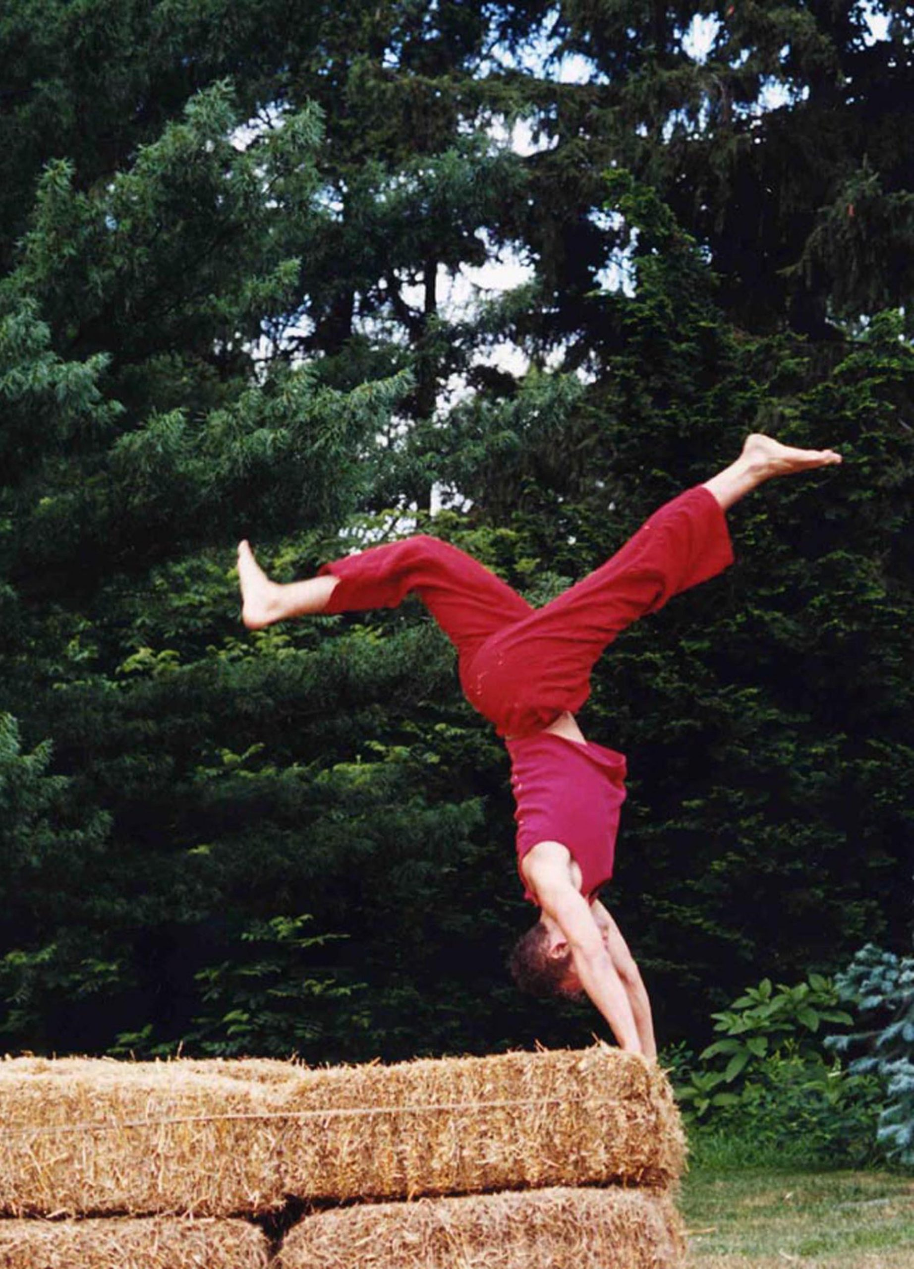 A dancer dressed in flowing red pants and skirt flips over bales of hay, upside down and legs spread.