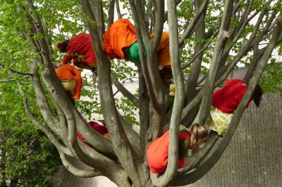 A number of people in bright, flowing clothes curl between and within the branches of a tree.