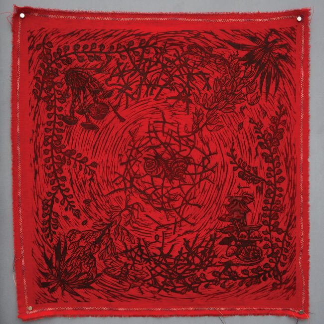 A red hanky with snail figures in the middle of a circle framed by sticks, ferns and mushrooms in black