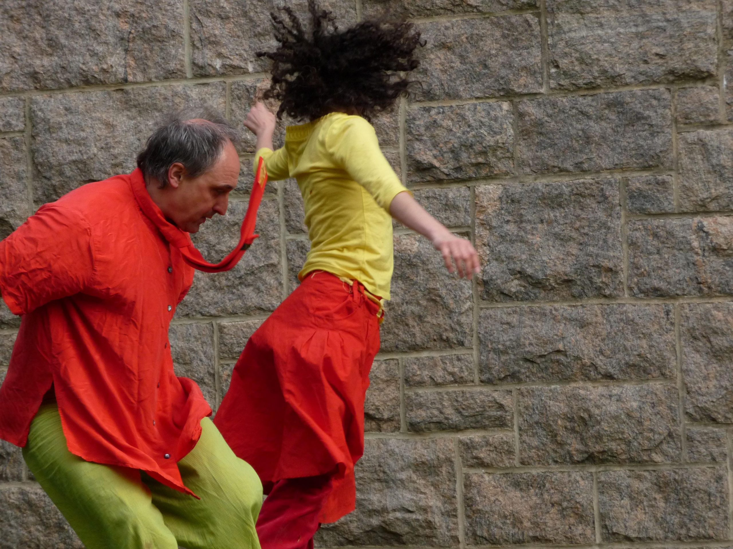 Two people dance before a stone wall, a man in red shirt and green pants falls back and a woman in yellow shirt and red skirt jumps forwards, looking away.