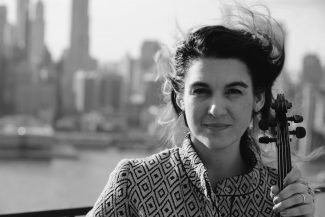 Black-and-white headshot of a woman with black hair pulled back, holding the neck of a violin and standing in front of a city waterfront, with the city skyline in the background.