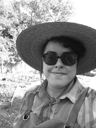 Image description: an olive-skinned Iranian person with short dark curly hair wears sunglasses, a straw hat, a brown apron, and a rainbow plaid shirt. They smile slightly. In the background is a garden and some trees.